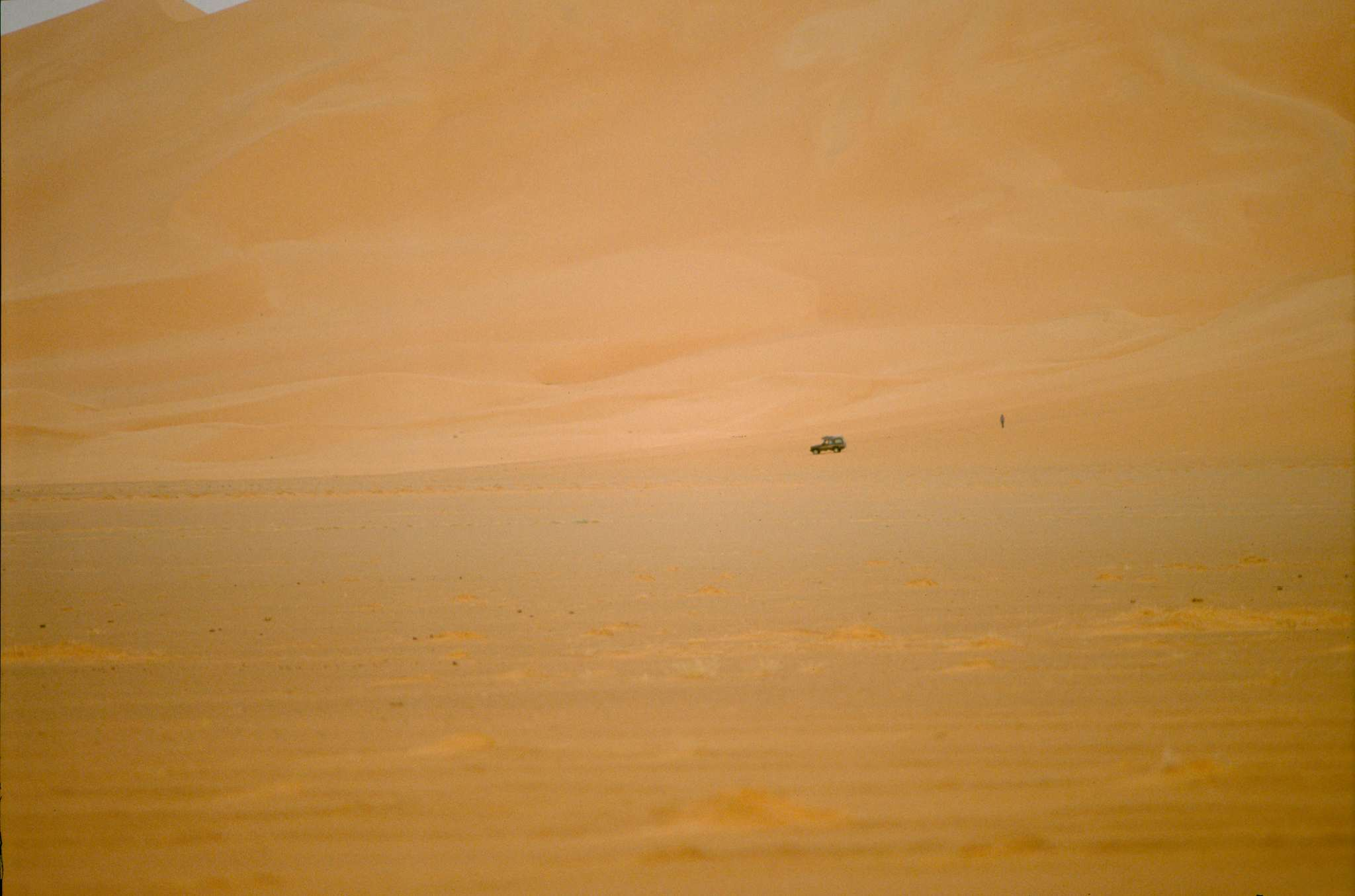 vehicle and man in dune landscape