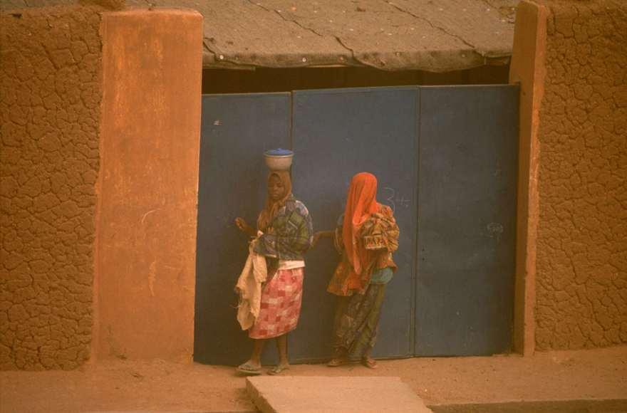 Three kids on the roadTwo women on the sidewalk in Agadez